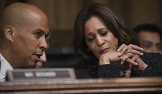 U.S. Sens. Cory Booker (L) and Kamala Harris (R) chat as Christine Blasey Ford, the woman accusing Supreme Court nominee Brett Kavanaugh of sexually assaulting her at a party 36 years ago, testifies before the U.S. Senate Judiciary Committee on Capitol Hill in Washington, D.C., Sept. 27, 2018.(Saul Loeb/Pool Photo via AP) ** FILE **