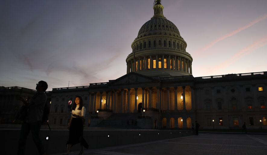 Shawn Gu and Julia Jiang, both of Beijing, walk past the U.S. Capitol after taking cell phone photographs using a light adaptor, Friday Sept. 28, 2018, in Washington. (AP Photo/Jacquelyn Martin)