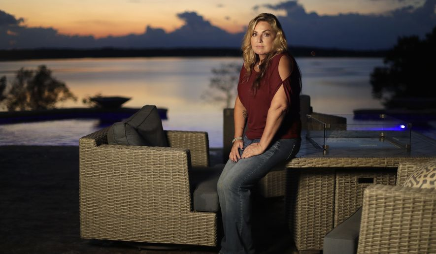 """In this Sept. 25, 2018, photo, Heather Melton sits on a patio at her home in Big Sandy, Tenn., as the sun sets over the Big Sandy River. Heather and her husband, Sonny Melton, were in the final stages of building the home when Sonny died when he was shot while protecting Heather at the Route 91 Harvest Festival mass shooting in Las Vegas on Oct. 1, 2017. Now a year later, many survivors, who were already bonded through the music, have formed a tight-knit, encouraging community as they heal, support and remember. They call themselves """"Country Strong."""" (AP Photo/Mark Humphrey)"""