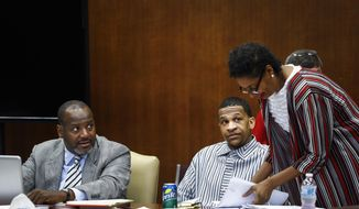 Defense attorneys Darla Palmer, right, and Alton Peterson, left, converse with defendant Quinton Tellis during Tellis' retrial, Friday, Sept. 28, 2018, in Batesville, Miss. Tellis is accused of killing Jessica Chambers near a small Mississippi town in 2014. A jury couldn't reach a verdict in Tellis' first trial last year. (Mark Weber/The Commercial Appeal via AP, Pool)