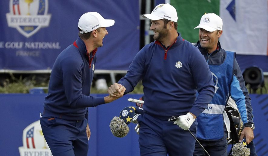Europe's Justin Rose, left, and Jon Rahm react after teeing off during their fourball match against Brooks Koepka of the US and Tony Finau on the opening day of the 42nd Ryder Cup at Le Golf National in Saint-Quentin-en-Yvelines, outside Paris, France, Friday, Sept. 28, 2018. (AP Photo/Matt Dunham)
