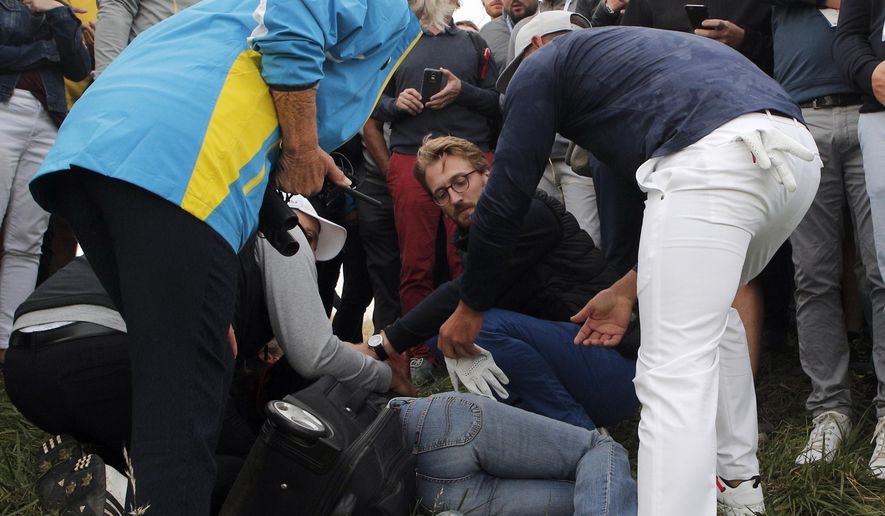 Brooks Koepka of the US offers a golf glove to an unidentified injured woman after his ball hit her on the 6th hole during a fourball match on the opening day of the 42nd Ryder Cup at Le Golf National in Saint-Quentin-en-Yvelines, outside Paris, France, Friday, Sept. 28, 2018. (AP Photo/Francois Mori)
