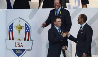Patrick Reed of the US, left, and Tiger Woods, touch fists, after being paired to play together on the first day during the opening ceremony of the Ryder Cup at Le Golf National in Saint-Quentin-en-Yvelines, outside Paris, France, Thursday, Sept. 27, 2018. The 42nd Ryder Cup will be held in France from Sept. 28-30, 2018 at Le Golf National. (AP Photo/Alastair Grant)