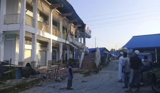 People survey a building partially damaged by earthquake in Poso, Central Sulawesi, Indonesia, Saturday, Sept. 29, 2018. A powerful earthquake rocked the Indonesian island of Sulawesi on Friday, triggering a 3-meter-tall (10-foot-tall) tsunami that an official said swept away houses in at least two cities. (AP Photo/Yoanes Litha)