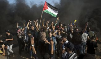 Palestinians chant slogans in front of black smoke rising from burning tires during a protest at the Gaza Strip's border with Israel, Friday, Sept.28, 2018. (AP Photo/Khalil Hamra)