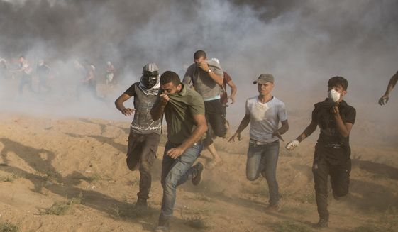 Palestinian protesters run for cover from teargas fired by Israeli troops during a protest at the Gaza Strip's border with Israel, Friday, Sept.28, 2018. (AP Photo/Khalil Hamra)