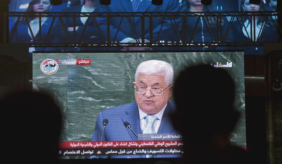 """Palestinians follow President Mahmoud Abbas's speech at the annual U.N. General Assembly, on a large screen in the West Bank city of Ramallah, Thursday, Sept. 27, 2018. Palestinian President Mahmoud Abbas declared Thursday that his people's rights """"are not up for bargaining"""" and he accused the U.S. of undermining the two-state solution, a day after President Donald Trump suggested for the first time in office that he """"liked"""" the long-discussed idea as the most effective way to resolve the Israeli-Palestinian conflict. (AP Photo/Nasser Nasser)"""