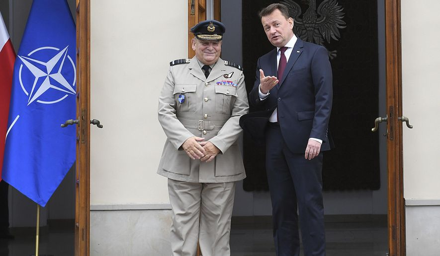 Poland's Defense Minister Mariusz Blaszczak, right, greets Chairman of the NATO Military Committee, Air Chief Marshal Sir Stuart Peach for talks ahead of the weekend session of military leaders from the alliance's 29 member nations, at the Defense Ministry in Warsaw, Poland, on Friday, Sept. 28, 2018. (AP Photo)