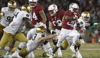 FILE - In this Nov. 25, 2017, file photo, Stanford running back Bryce Love (20) breaks through the line for a first down against Notre Dame during the second half of an NCAA college football game in Stanford, Calif. Fresh from its come-from-behind 38-31 OT victory at Oregon, No. 7 Stanford visits No. 8 Notre Dame on Saturday. The Irish will attempt to end a three-game losing streak in the series and stay unbeaten.  (AP Photo/Tony Avelar, File)