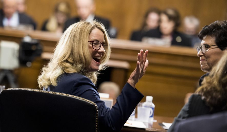 Christine Blasey Ford waves as she testifies before the Senate Judiciary Committee, Thursday, Sept, 27, 2018 on Capitol Hill in Washington.  (Tom Williams/Pool Image via AP)
