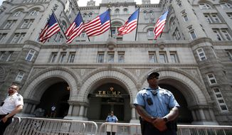 In this June 30, 2018, photo, law enforcement officers stand guard in front of the Trump Hotel in Washington. (AP Photo/Alex Brandon) **FILE**