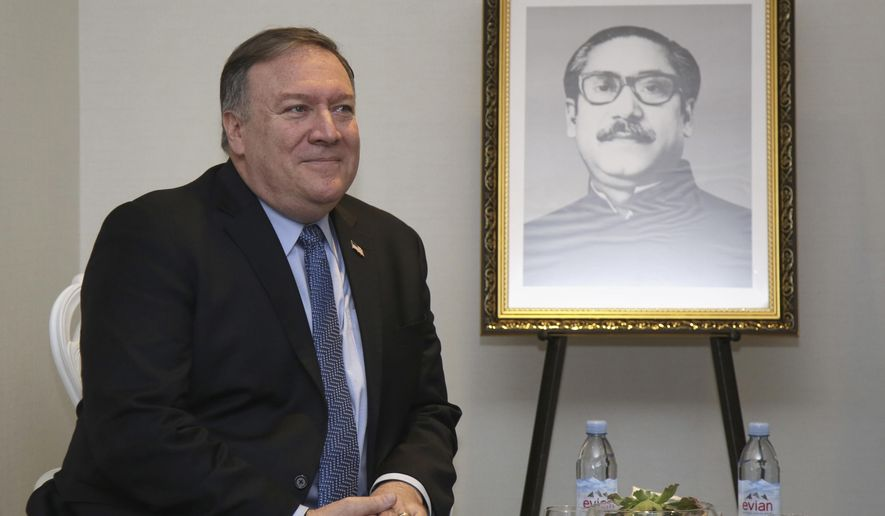 Mike Pompeo, the United States Secretary of State, sits next to a picture of Sheikh Mujibur Rahman, the founding father of Bangladesh, as he waits for the start of meeting with their Prime Minister in New York, Friday, Sept. 28, 2018. In the background is a picture of . (AP Photo/Seth Wenig)