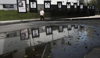 In this Sept. 26, 2018 photo, photographs of the teachers college students who disappeared on Sept. 26, 2014 hang on the fence surrounding the Senate building in Mexico City. President-elect Andres Manuel Lopez Obrador said Wednesday his administration will accept a truth commission to investigate the case of the 43 missing students, drawing rare praise and expressions of hope from the long-suffering parents of the victims. (AP Photo/Rebecca Blackwell)