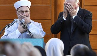 Turkish President Recep Tayyip Erdogan, right, and Diyanet President Ali Eras cover their faces during a prayer on occasion of the opening of the new mosque in Cologne, Germany, on Saturday, Sept. 29, 2018. (AP Photo/Martin Meissner)