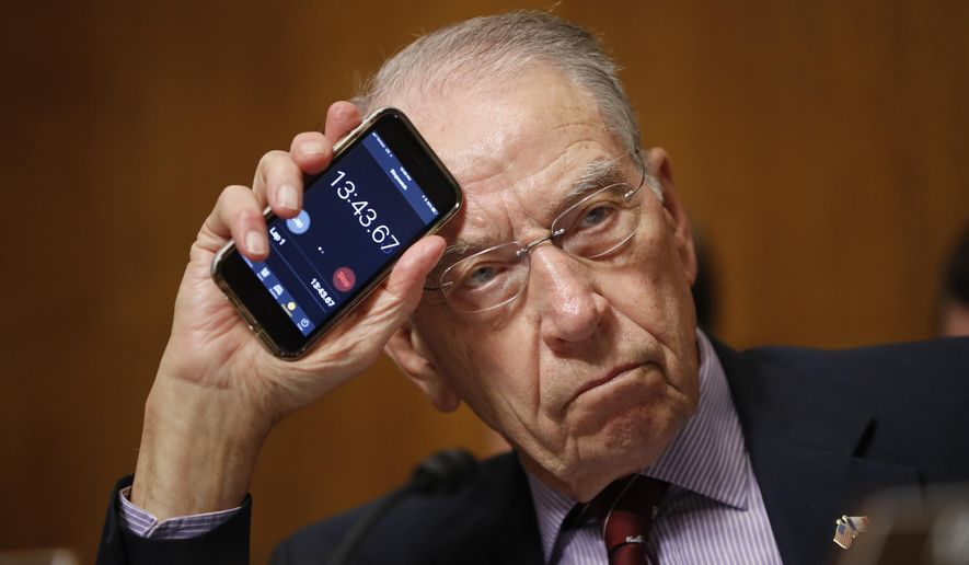 Senate Judiciary Committee Chairman Chuck Grassley of Iowa holds up a timer on a smartphone to show Sen. Cory Booker, D-N.J., how long he has been speaking for during a Senate Judiciary Committee hearing on Supreme Court nominee Judge Brett Kavanaugh, Friday, Sept. 28, 2018, on Capitol Hill in Washington. The committee advanced Brett Kavanaugh's nomination for the Supreme Court after agreeing to a late call from Sen. Jeff Flake, R-Ariz., for a one-week investigation into sexual assault allegations against the high court nominee. (AP Photo/Pablo Martinez Monsivais)