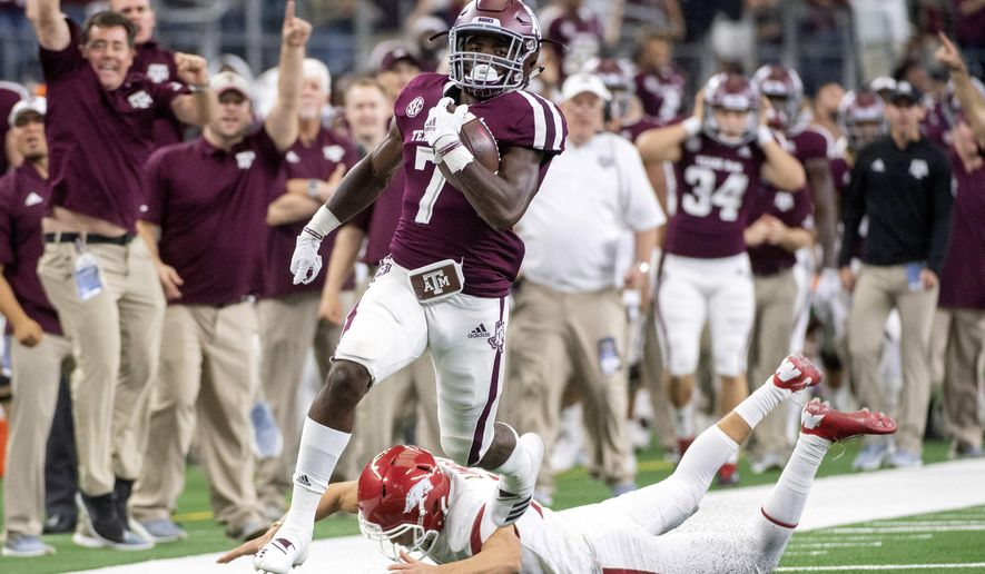 Texas A&M kick returner Jashaun Corbin (7) avoids the diving tackle of Arkansas kicker Connor Limpert as he returns the opening kickoff for a touchdown during the first quarter of an NCAA college football game Saturday, Sept. 29, 2018, in Arlington, Texas. (AP Photo/Jeffrey McWhorter)