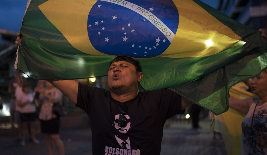 A man sing the Brazil's national anthem as he waves the national flag in support leading presidential candidate Jair Bolsonaro, outside Bolsonaro's residence in Rio de Janeiro, Brazil, Saturday, Sept. 29, 2018. Bolsonaro, who suffered intestinal damage and severe internal bleeding after the Sept. 6 attack at a campaign event and has undergone multiple surgeries, was discharged Saturday from a Sao Paulo hospital where he was being treated. (AP Photo/Leo Correa)