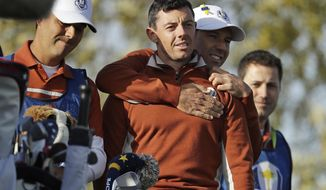 Europe's Sergio Garcia, second right, embraces Europe's Rory McIlroy on the 7th tee during a fourball match on the second day of the 42nd Ryder Cup at Le Golf National in Saint-Quentin-en-Yvelines, outside Paris, France, Saturday, Sept. 29, 2018. (AP Photo/Matt Dunham)