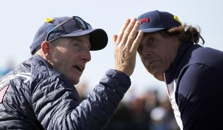 US team captain Jim Furyk gestures while speaking with his player Phil Mickelson during a fourball match on the second day of the 2018 Ryder Cup at Le Golf National in Saint Quentin-en-Yvelines, outside Paris, France, Saturday, Sept. 29, 2018. (AP Photo/Francois Mori)
