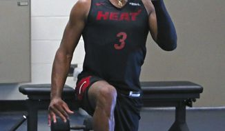 Miami Heat NBA basketball player Dwyane Wade uses a weight at the team's training camp in Boca Raton, Fla., Friday, Sept. 28, 2018. (David Santiago/Miami Herald via AP)