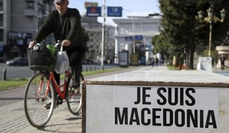 "A man on his bicycle passes a sign that reads in French: ""I am Macedonia"" written by opponents of the referendum in Skopje, Friday, Sept. 28, 2018. A referendum set for Sunday in Macedonia seeks voter support for changing the Balkan nation's name to North Macedonia. Greece has agreed to drop longstanding objections to neighboring Macedonia joining NATO and eventually becoming a member of the European Union, if the new name is approved. (AP Photo/Thanassis Stavrakis)"