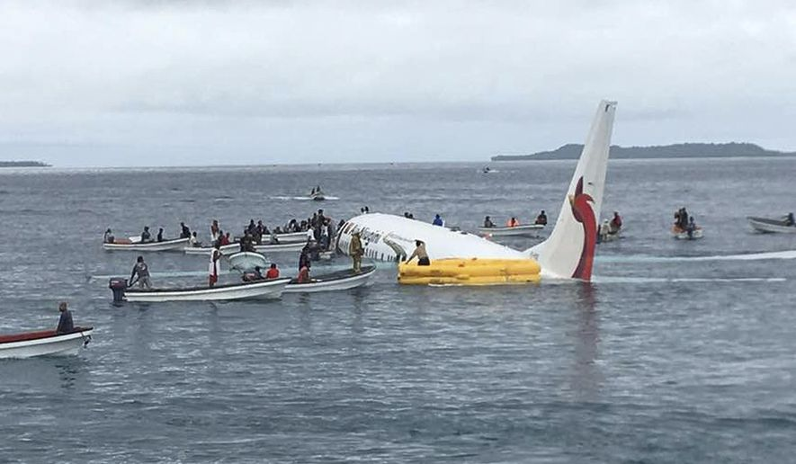 FILE - In this Sept. 28, 2018, file photo, local fishing boats move in to recover the passengers and crew of Air Niugini flight following the plane crashing into the sea on its approach to Chuuk International Airport in the Federated States of Micronesia. The airline operating a flight that crashed into a Pacific lagoon on Friday in Micronesia now says that one man is missing, after earlier saying that all 47 passengers and crew had safely evacuated the sinking plane. (James Yaingeluo via AP, File)