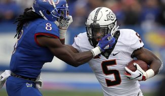 Oklahoma State running back Justice Hill (5) is tackled by Kansas cornerback Shakial Taylor (8) during the first half of an NCAA college football game in Lawrence, Kan., Saturday, Sept. 29, 2018. (AP Photo/Orlin Wagner)