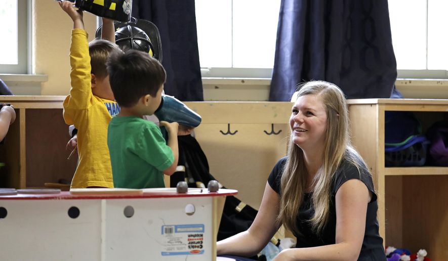 In this file photo taken Aug. 27, 2018, director Jenny Cimbalnik talks with children at the Wallingford Child Care Center in Seattle.  (AP Photo/Elaine Thompson, File) **FILE**