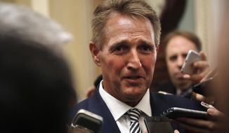 Sen. Jeff Flake, R- Ariz., is questioned by reporters about Supreme Court nominee Brett Kavanaugh, Friday Sept. 28, 2018, on Capitol Hill in Washington. After a flurry of last-minute negotiations, the Senate Judiciary Committee advanced Brett Kavanaugh's nomination for the Supreme Court after agreeing to a late call from Sen. Flake for a one week investigation into sexual assault allegation against the high court nominee. (AP Photo/Jacquelyn Martin)