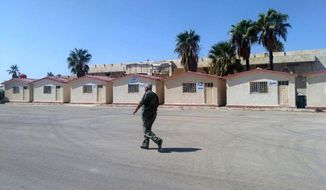 In this photo released by the Syrian official news agency SANA, a Syrian soldier walk inside the Naseeb crossing point with Jordan, Syria, Saturday, Sept 29, 2018. Preparations to reopen a vital border crossing between Syria and Jordan have been completed, setting the stage for its reopening on Oct. 10, Syria's state-run news agency said Saturday. (SANA via AP)