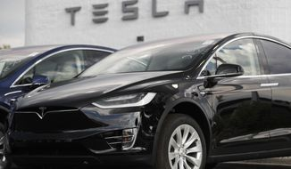 FILE - In this July 8, 2018 file photo, a 2018 Model X sits on display outside a Tesla showroom in Littleton, Colo.  Elon Musk's murky future as Tesla Motors' CEO amid a securities fraud lawsuit isn't the only cloud hanging over the electric car maker.  The company was on shaky financial ground even before government regulators set out to remove Musk, a blow that has increased the pressure on Tesla to prove it can consistently manufacture enough cars to survive.  (AP Photo/David Zalubowski, File)