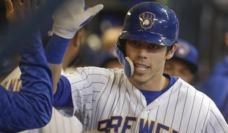 Milwaukee Brewers' Christian Yelich is congratulated after hitting a two-run home run during the first inning of a baseball game against the Detroit Tigers Friday, Sept. 28, 2018, in Milwaukee. (AP Photo/Morry Gash)