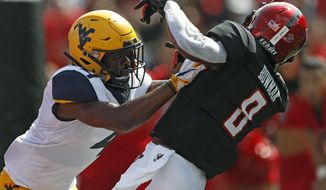 West Virginia's Josh Norwood (4) breaks up a pass meant for Texas Tech's De'Quan Bowman (8) during the first half of an NCAA college football game Saturday, Sept. 29, 2018, in Lubbock, Texas. (AP Photo/Brad Tollefson)