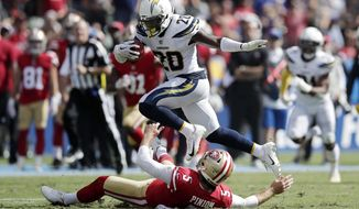 Los Angeles Chargers defensive back Desmond King, top, jumps over San Francisco 49ers punter Bradley Pinion while returning a punt during the first half of an NFL football game, Sunday, Sept. 30, 2018, in Carson, Calif. (AP Photo/Jae Hong)