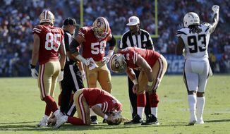San Francisco 49ers quarterback C.J. Beathard, below, is seen to by teammates after getting tackled by Los Angeles Chargers defensive back Casey Hayward as Chargers defensive end Darius Philon, right, celebrates during the second half of an NFL football game, Sunday, Sept. 30, 2018, in Carson, Calif. (AP Photo/Marcio Sanchez)