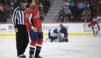 Washington Capitals right wing Tom Wilson (43) is escorted by an official off the ice after he checked St. Louis Blues center Oskar Sundqvist, on ice at back center, during the second period of an NHL preseason hockey game, Sunday, Sept. 30, 2018, in Washington. (AP Photo/Nick Wass)