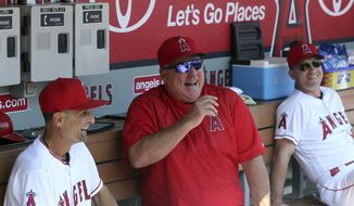 Los Angeles Angels manager Mike Scioscia, middle, laughs in the dugout before a baseball game between the Angels and the Oakland Athletics in Anaheim, Calif., Sunday, Sept. 30, 2018. It is expected that this will be Scioscia's last game as manager of the Angels. (AP Photo/Reed Saxon)
