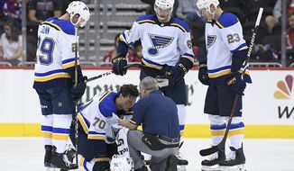 St. Louis Blues center Oskar Sundqvist (70), of Sweden, is tended to by a trainer after he was checked by Washington Capitals right wing Tom Wilson, not seen, during the second period of an NHL preseason hockey game, Sunday, Sept. 30, 2018, in Washington. Also seen are Blues defenseman Vince Dunn (29), St. Louis Blues left wing Mackenzie MacEachern (62) and St. Louis Blues right wing Dmitrij Jaskin (23), of Russia. (AP Photo/Nick Wass)
