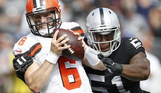 Cleveland Browns quarterback Baker Mayfield (6) tries to escape the grasp of Oakland Raiders defensive end Bruce Irvin (51) during the first half of an NFL football game in Oakland, Calif., Sunday, Sept. 30, 2018. (AP Photo/D. Ross Cameron)