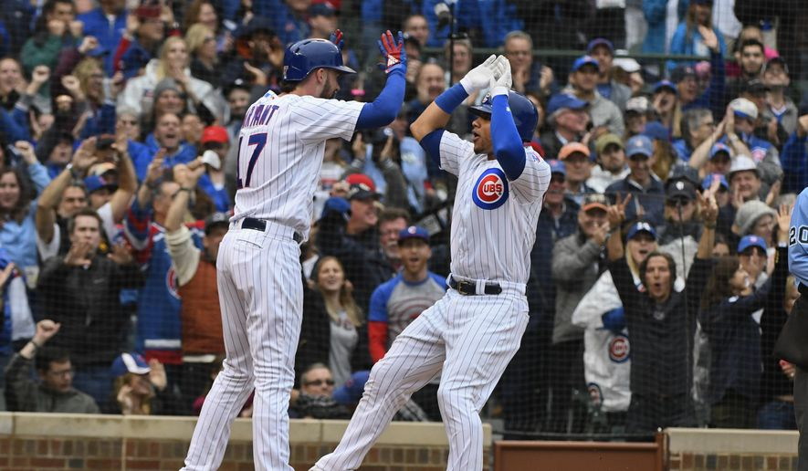 Chicago Cubs' Kris Bryant (17) and Willson Contreras, right, high five after they score on Contreras' home run during the fifth inning of a baseball game against the St. Louis Cardinals on Sunday, Sept. 30, 2018, in Chicago. (AP Photo/Matt Marton)