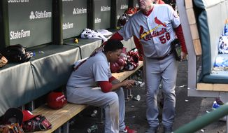 St. Louis Cardinals shortstop Yairo Munoz, seated, gets a pat on the back from batting coach Mark Budaska (58) after a baseball game against the Chicago Cubs on Sunday, Sept. 30, 2018, in Chicago. The Chicago Cubs won 10-5. (AP Photo/Matt Marton)