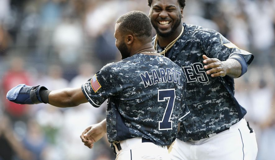 San Diego Padres' Franmil Reyes, right, congratulates Manuel Margot, left, after Margot slides safely into home from third base, after Arizona Diamondbacks catcher John Ryan Murphy threw to first to get Francisco Mejia, after striking out swinging during the 10th inning of a baseball game in San Diego, Sunday, Sept. 30, 2018. The Padres won 4-3, in 10 innings. (AP Photo/Alex Gallardo)