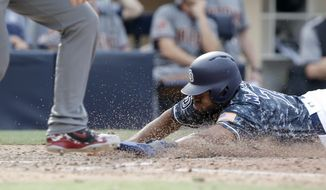 San Diego Padres' Manuel Margot, right, slides into home safely after Arizona Diamondbacks catcher John Ryan Murphy threw to first to get Francisco Mejia after striking out swinging during the 10th inning of a baseball game in San Diego, Sunday, Sept. 30, 2018. The Padres won 4-3 in 10 innings. (AP Photo/Alex Gallardo)