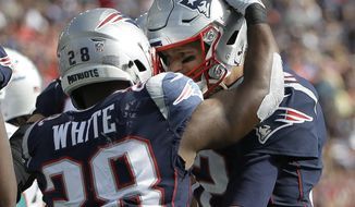 New England Patriots quarterback Tom Brady, right, congratulates running back James White on his touchdown run against the Miami Dolphins during the first half of an NFL football game, Sunday, Sept. 30, 2018, in Foxborough, Mass. (AP Photo/Steven Senne)