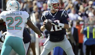 New England Patriots quarterback Tom Brady (12) looks for a receiver under pressure from Miami Dolphins defensive back T.J. McDonald (22) during the first half of an NFL football game, Sunday, Sept. 30, 2018, in Foxborough, Mass. (AP Photo/Elise Amendola)