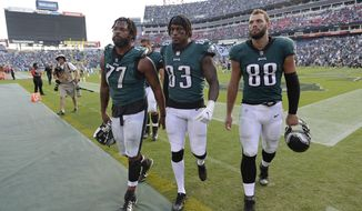 Philadelphia Eagles defensive end Michael Bennett (77), tight end Josh Perkins (83) and tight end Dallas Goedert (88) leave the field after losing to the Tennessee Titans in overtime of an NFL football game Sunday, Sept. 30, 2018, in Nashville, Tenn. The Titans won 26-23. (AP Photo/Mark Zaleski)