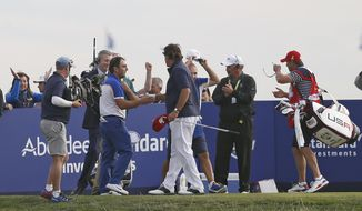 Phil Mickelson of the US concedes his singles match to Europe's Francesco Molinari for Europe to clinch the Ryder Cup on the final day of the 42nd Ryder Cup at Le Golf National in Saint-Quentin-en-Yvelines, outside Paris, France, Sunday, Sept. 30, 2018. (AP Photo/Alastair Grant)