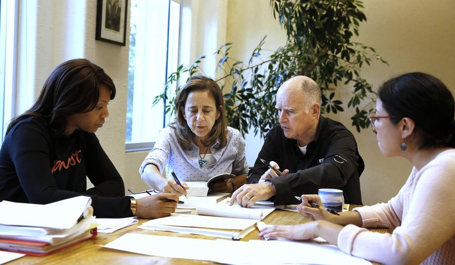 Gov. Jerry Brown reviews a measure with his wife, Anne Gust Brown, second from left, as staff members Camille Wagner, left, and Graciela Castillo-Krings, right, look on at his Capitol office, Sunday, Sept. 30, 2018, in Sacramento, Calif. Sunday is the last day for Brown to approve or veto bills passed by the legislature. Brown, who will be leaving office in January, is acting on some on the last pieces of legislation in his tenure as governor. (AP Photo/Rich Pedroncelli)