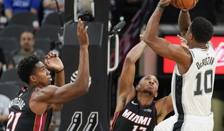 San Antonio Spurs' DeMar DeRozan (10) shoots against Miami Heat's Hassan Whiteside (21) and Rodney McGruder during the first half of an NBA preseason basketball game, Sunday, Sept. 30, 2018, in San Antonio. (AP Photo/Darren Abate)