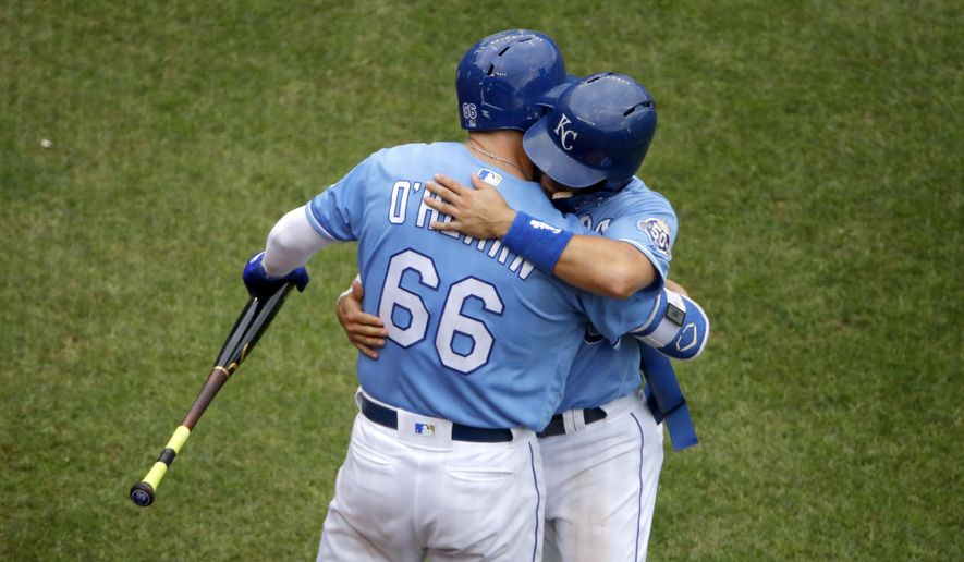 Kansas City Royals' Whit Merrifield hugs Ryan O'Hearn (66) after Merrifield came out of the game during the eighth inning of a baseball game Sunday, Sept. 30, 2018, in Kansas City, Mo. (AP Photo/Charlie Riedel)